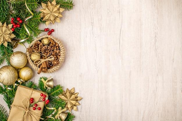 Composizione natalizia su legno per i saluti delle vacanze invernali. regalo di natale, cestino tradizionale, stelle di anice, pigne, bastoncini di cannella, noci e campane, vischio e palline di natale