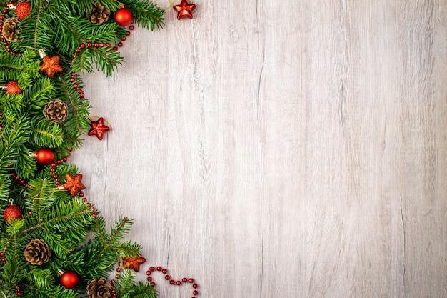 Composizione natalizia su legno per i saluti delle vacanze invernali. sfere e stelle rosse di natale, pigne, stringa rossa su un legno strutturato.