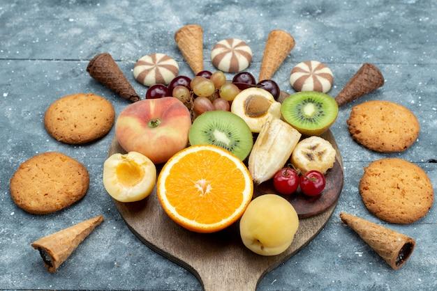 Composizione nella frutta di vista superiore affettata e intera con i biscotti sul biscotto esotico della frutta luminosa dello scrittorio