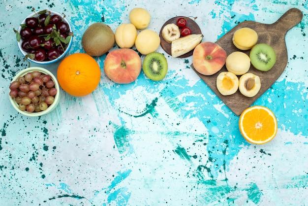 Composizione nella frutta vista dall'alto affettata e intera con i biscotti sullo zucchero esotico del biscotto della frutta blu-luminosa del fondo