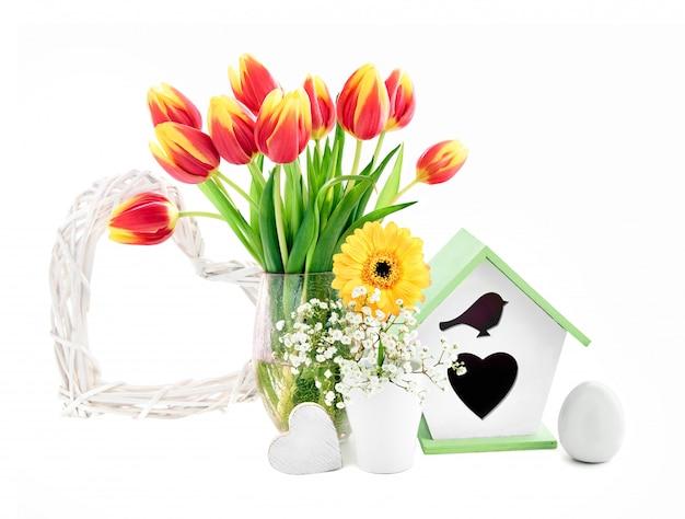 Composizione nella primavera con i fiori, il nido per deporre le uova, l'uovo ed il cuore, isolati su bianco