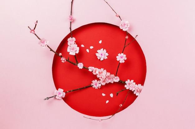 Composizione papercraft primavera con ramo di sakura su rosa e rosso