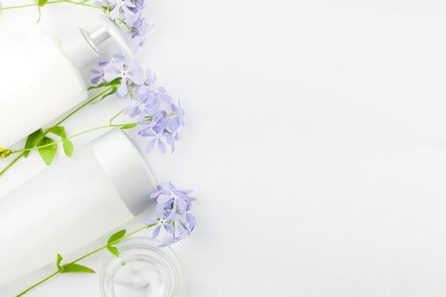 Composizione pastello di cosmetici e fiori