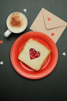 Composizione per carta di san valentino con caffè, enveloope e sandwich a forma di cuore