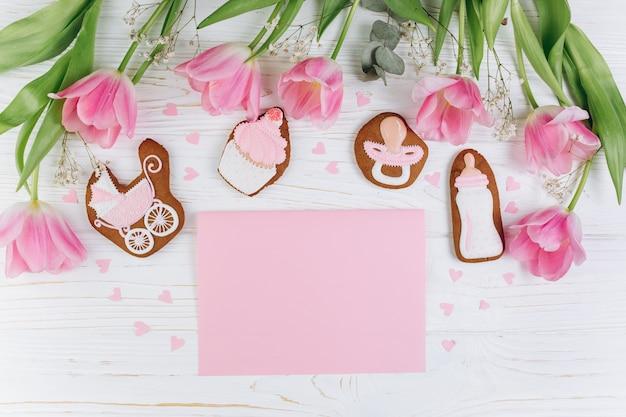 Composizione per neonati su fondo in legno con tulipani rosa, cuori e biscotti