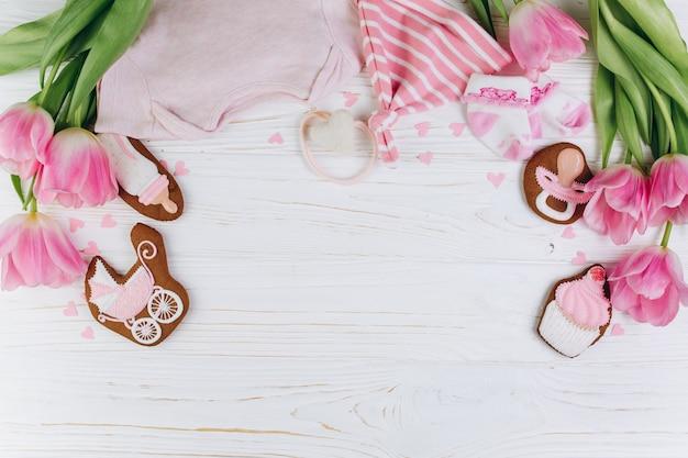 Composizione per neonati su uno sfondo in legno con vestiti, tulipani rosa, cuori.