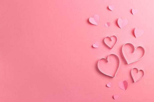 Composizione per san valentino. delicato sfondo rosa e cuori rosa tagliati fuori dalla carta. biglietto d'auguri. vista piana, vista dall'alto, copia spazio.