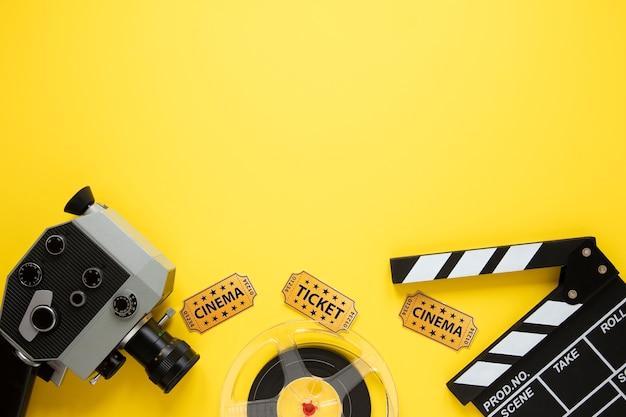 Composizione piana laica degli elementi del cinema su fondo giallo con lo spazio della copia