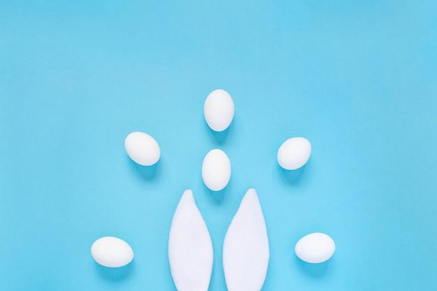 Composizione piana laica delle orecchie creative del coniglietto di pasqua su fondo blu, spazio per testo