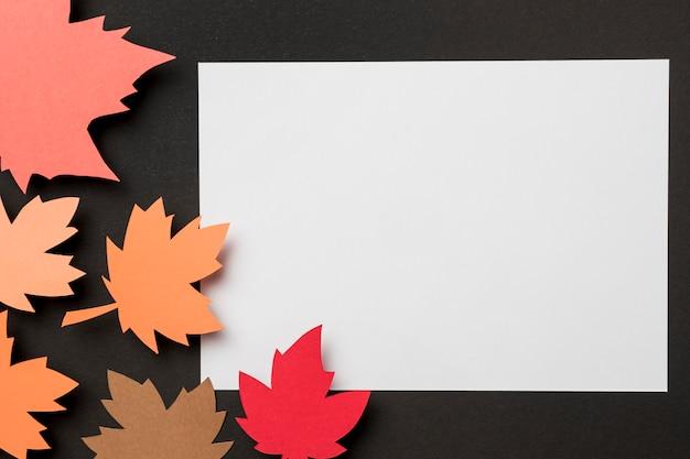 Composizione piana nelle foglie di autunno della carta di disposizione su libro bianco