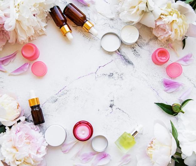 Composizione piatta con fiori di peonia e cosmetici naturali