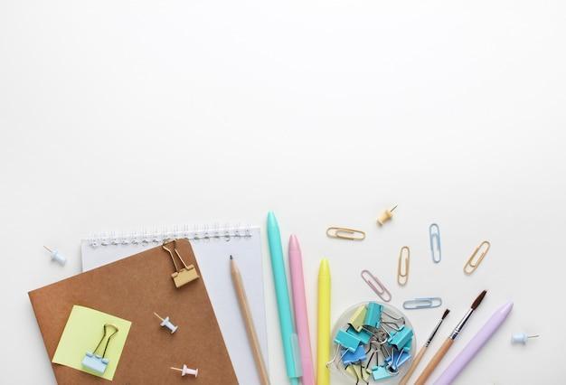 Composizione piatta di quaderni, penne, matita, raccoglitori, foglietti adesivi, graffette e pennelli.