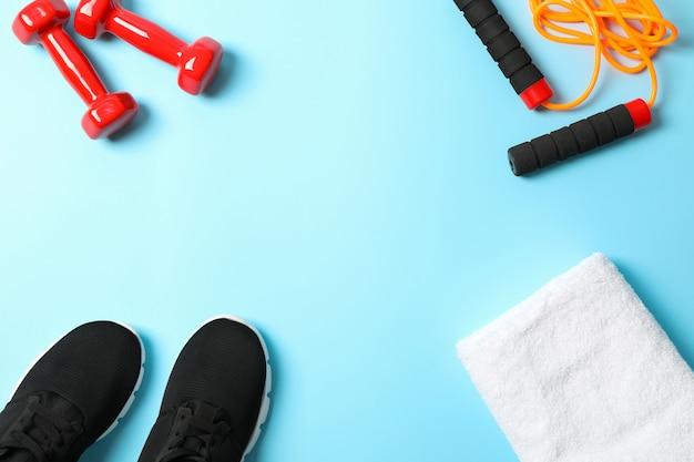 Composizione piatta laica con accessori sport lifestyle su sfondo blu