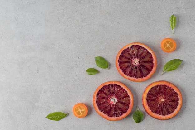 Composizione piatta laica con arance rosse a fette e frutti kumquat su sfondo grigio, copia del testo dello spazio