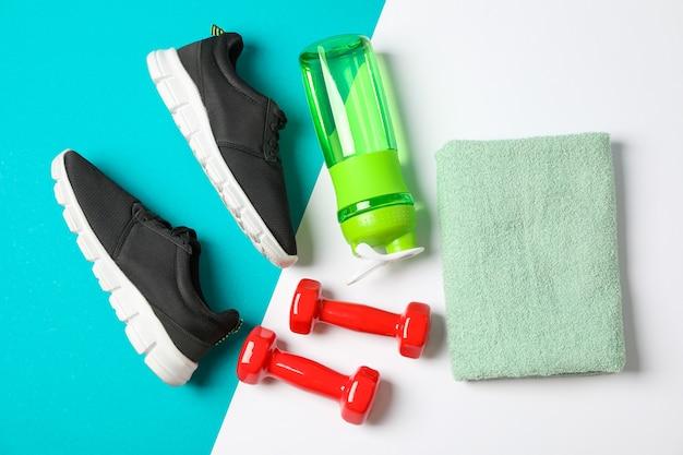 Composizione piatta laica con asciugamano, manubri, bottiglia fitness e scarpe da ginnastica su sfondo colorato