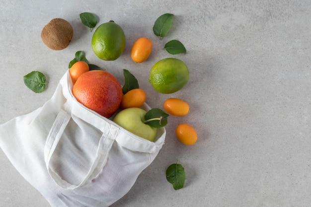 Composizione piatta laica con borsa eco e frutti tropicali sparsi su sfondo grigio, spazio per il testo