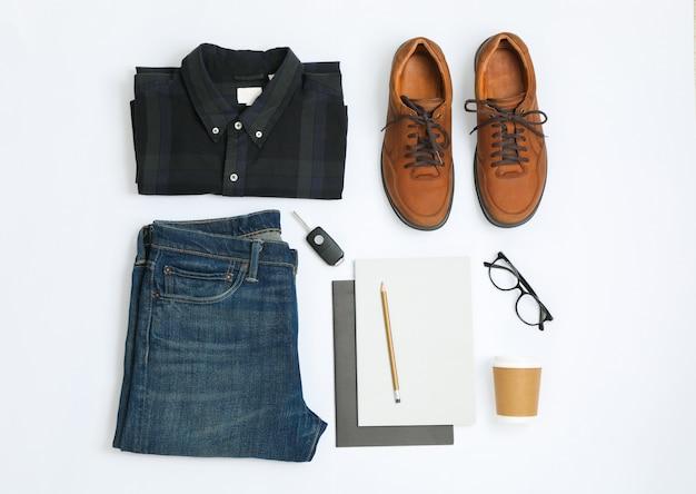 Composizione piatta laica con camicia, jeans, scarpe e occhiali su sfondo bianco