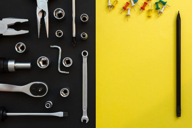 Composizione piatta laica con diversi strumenti di costruzione su sfondo nero e giallo. vista dall'alto di lista di controllo e strumenti di lavoro, chiave inglese, cacciavite, pinza, matita.