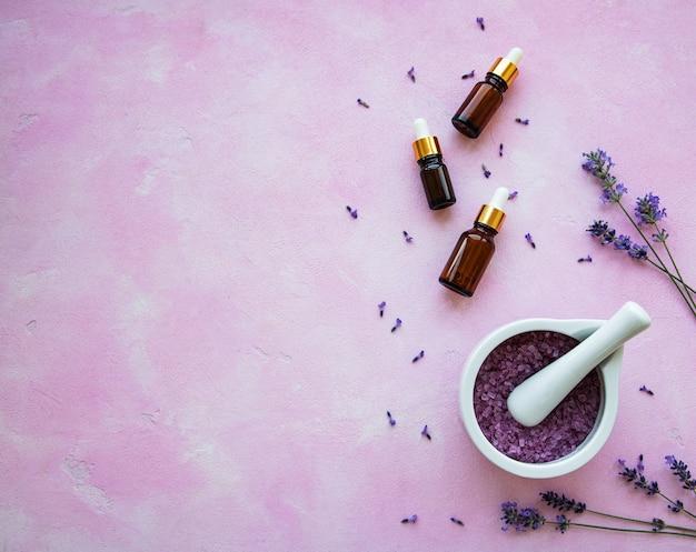 Composizione piatta laica con fiori di lavanda e cosmetici naturali su sfondo rosa