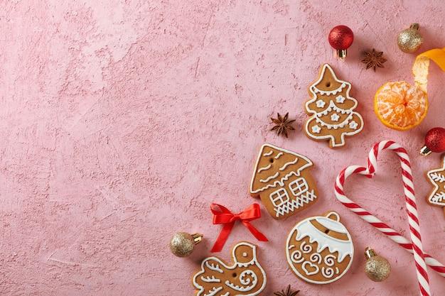 Composizione piatta laica con gustosi biscotti natalizi fatti in casa, mandarino, caramelle su rosa, spazio per il testo. vista dall'alto