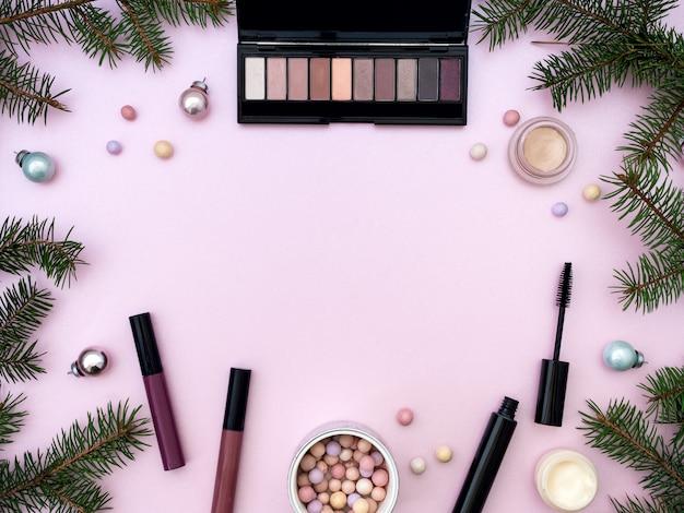 Composizione piatta laica con prodotti cosmetici trucco e decorazioni di natale su sfondo rosa. vista dall'alto, copia spazio