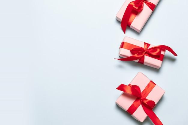 Composizione piatta laica con scatole rosa con nastri di raso rosso su sfondo blu per il compleanno