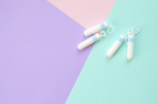 Composizione piatta laica con tamponi mestruali su sfondo blu pastello rosa e lilla
