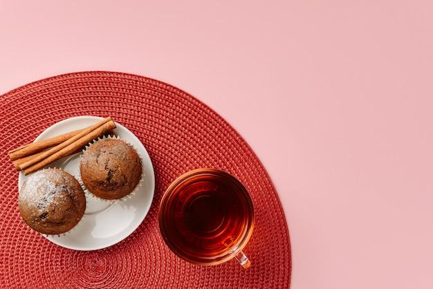 Composizione piatta laica con una tazza di tè, muffin e bastoncini di cannella sdraiato su un tovagliolo rosso, isolato su una parete rosa con spazio per il testo.