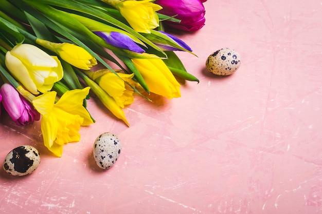 Composizione piatta laica di pasqua. un bouquet di fiori primaverili e uova di quaglia