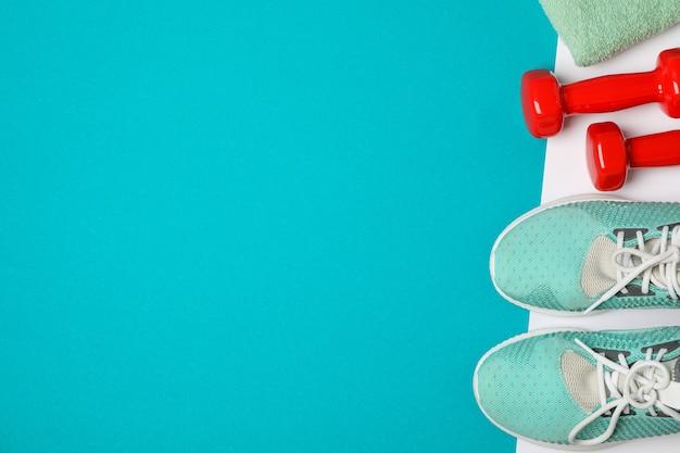 Composizione piatta laici con manubri, asciugamano e scarpe da ginnastica sul colore di sfondo