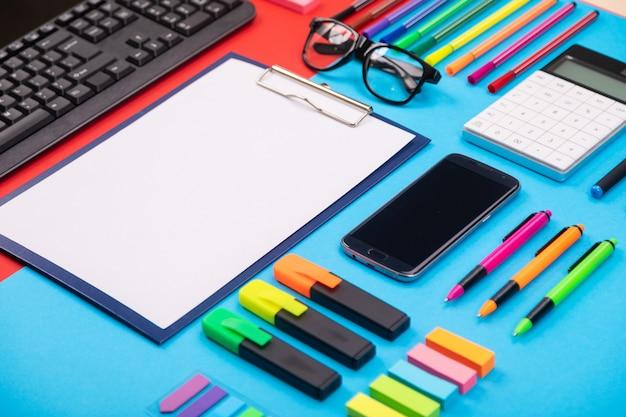 Composizione piatta laici di business desk con smartphone, appunti, adesivi e penna su colorato blu e rosso