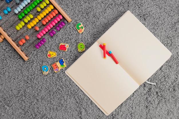 Composizione piatta laici di giocattoli e modello di libro aperto