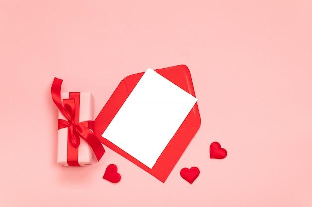 Composizione romantica con confezione regalo a sorpresa, fiocco in nastro rosso, busta rossa con carta sul rosa
