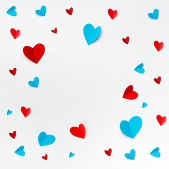 Composizione romantica fatta con cuori rossi su sfondo bianco con copyspace per il testo