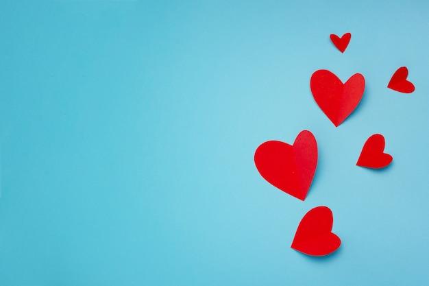 Composizione romantica fatta con cuori rossi su sfondo blu con copyspace per il testo