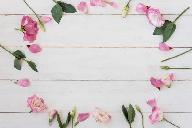 Composizione rosa dei fiori e delle foglie sulla tavola