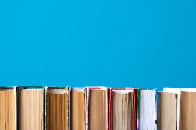 Composizione semplice di libri con copertina rigida, libri grezzi sulla tavola di ponte di legno e blu