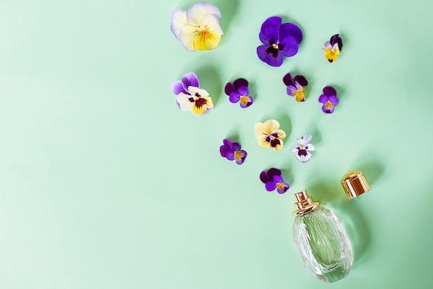 Composizione, set con bellissimi fiori freschi colorati, flacone profumato e spray con profumo femminile. viole. vista dall'alto. disteso.