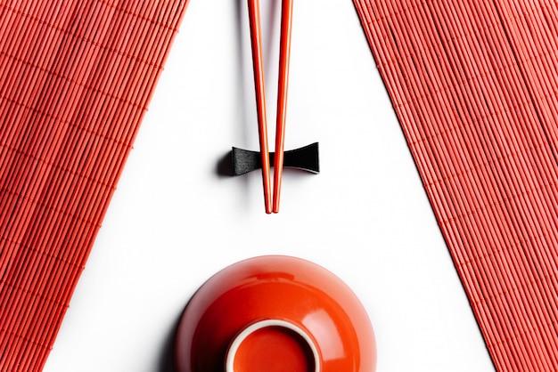 Composizione simmetrica con bacchette rosse, tovaglioli di bambù e una tazza isolata sul muro bianco.
