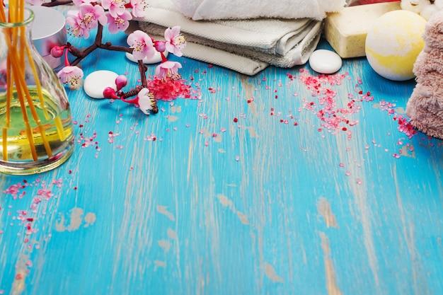 Composizione spa con asciugamani in cotone, olio aromatico, sale marino e pietre sul blu