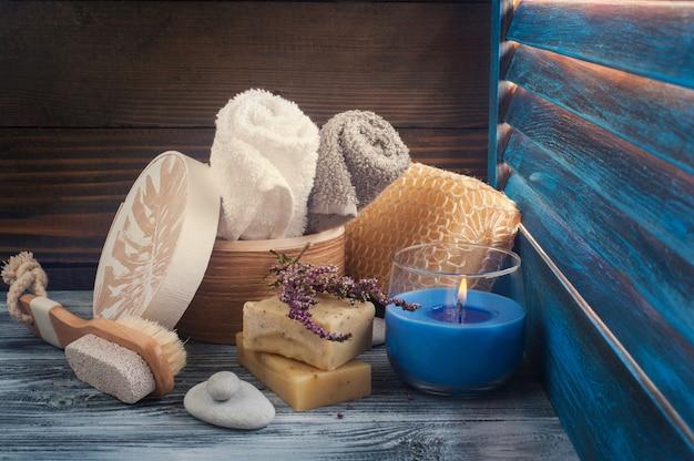 Composizione spa con asciugamani, sapone, pennello, candela accesa