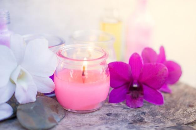 Composizione spa con lume di candela rosa aromatico e fiore di orchidea