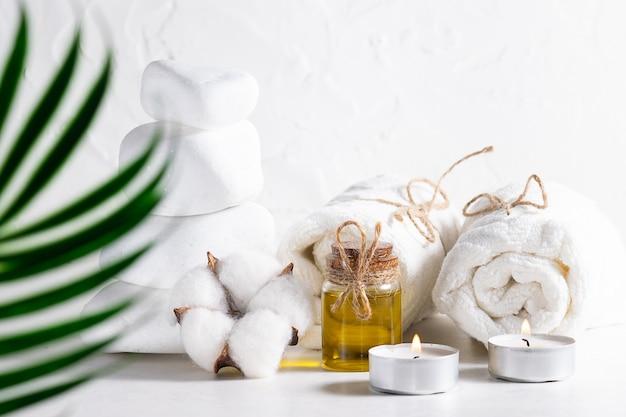 Composizione spa con olio essenziale, massaggio pietre, candele e asciugamani su sfondo bianco di cemento.