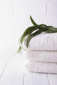 Composizione spa sul tavolo di legno. pila di tre soffici asciugamani bianchi con ramo di eucalipto.