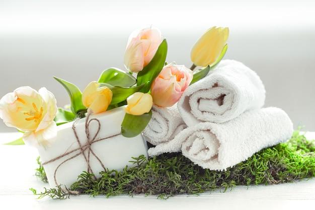 Composizione spring spa con articoli per la cura del corpo con tulipani freschi su sfondo chiaro, bellezza e salute.