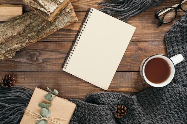 Composizione stile flatlay hygge con sciarpa lavorata a maglia da donna di moda, taccuino di carta bianca, tazza di tè, confezione regalo, legna da ardere