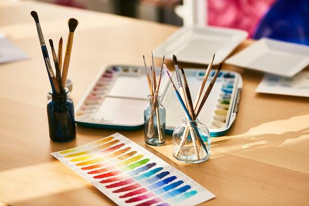 Composizione sul posto di lavoro dell'artista, occhiali con pennelli e campioni