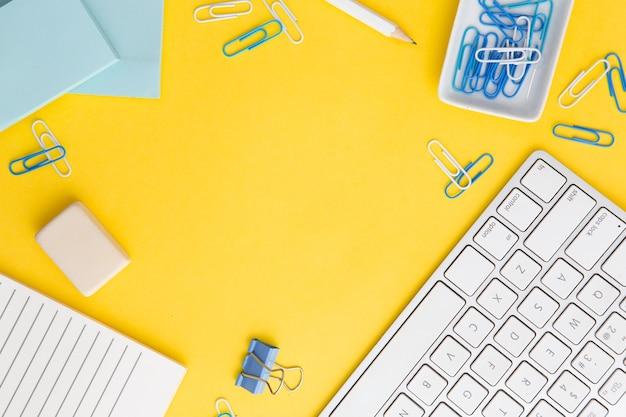 Composizione sul posto di lavoro su sfondo giallo con spazio di copia
