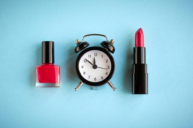 Composizione sveglia nera con cosmetici su priorità bassa blu