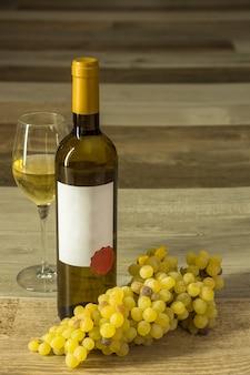 Composizione verticale della bottiglia di vino bianco con vetro etichetta bianca e uva bianca